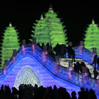In this photo taken Friday, visitors walk over an ice bridge built next to colorful pagodas, also made from blocks of ice, at the annual Harbin International Ice and Snow festival in Harbin, a city in northeastern's China's Heilongjiang province. | AP