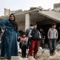 Syrians stand next to debris and rubble from buildings damaged by reported airstrikes in the rebel-held town of Orum al-Kubra, in the northern Syrian province of Aleppo, on Jan. 5. Airstrikes by Syrian regime ally Russia hit the west of Aleppo province late on Jan. 4, the first such raids in the area since a deal between Moscow and rebel backer Ankara to stave off a massive regime offensive on the wider Idlib region in September. | AFP-JIJI