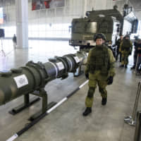 A Russian military officer walks past a 9M729 land-based cruise missile on display with its launcher in Kubinka, outside Moscow, on Jan. 23. The Russian military has spelled out the specifications of its new missile, seeking to dispel the U.S. claim that the weapon violates a key nuclear arms pact. | AP