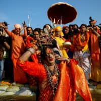 Laxmi Narayan Tripathi, chief of the Kinnar Akhara congregation for transgender people, takes a dip during the first Shahi Snan (grand bath) during the Kumbh Mela (Pitcher Festival), in Prayagraj (formerly Allahabad), in northern India on Jan. 15. | REUTERS