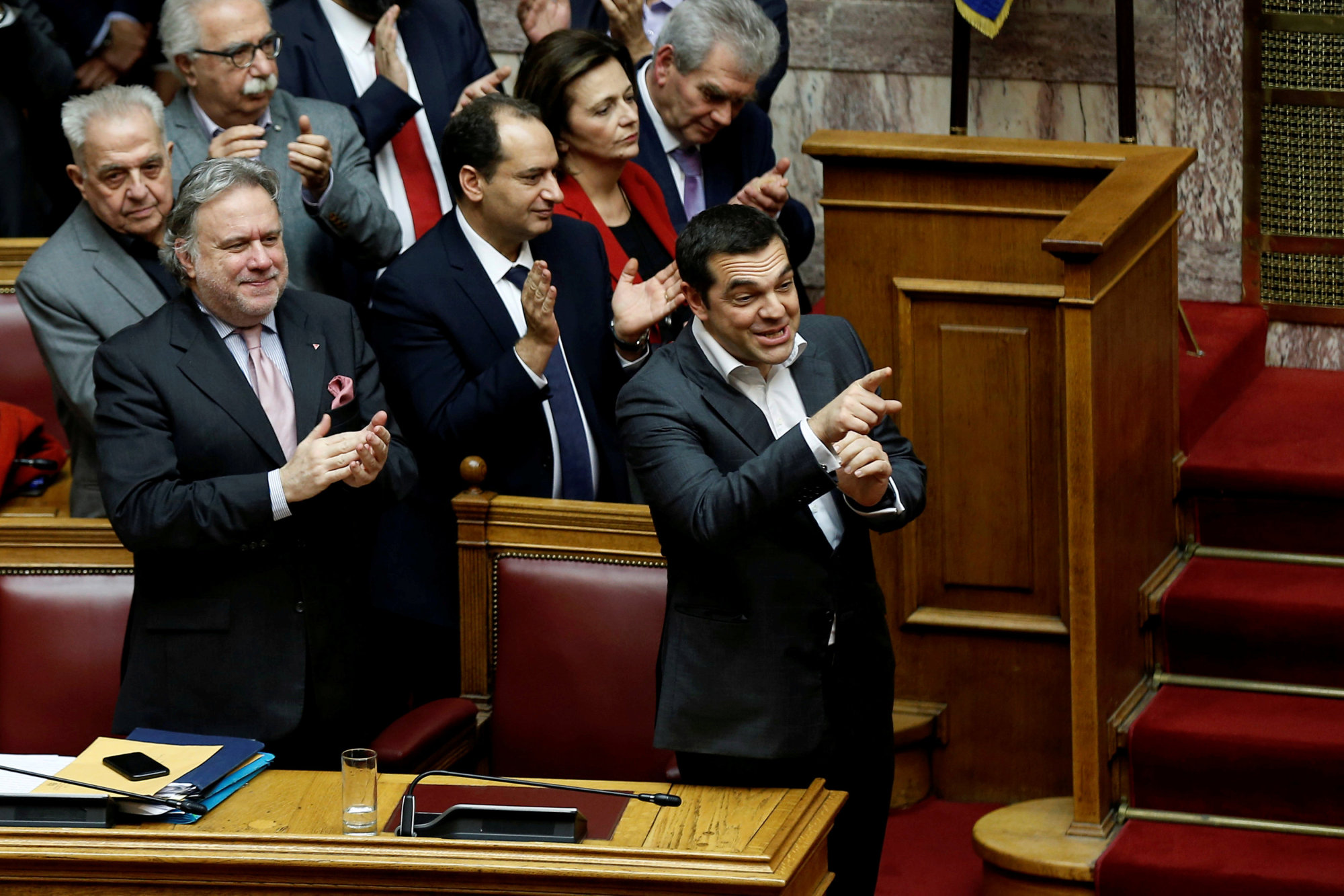 Greek Prime Minister Alexis Tsipras and members of his government applaud after a vote on an accord between Greece and Macedonia changing the former Yugoslav republic's name in Athens on Friday.   REUTERS