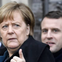 German chancellor Angela Merkel and French President Emmanuel Macron leave after the signing of a new Germany-France friendship treaty at the historic Town Hall in Aachen, Germany, on Tuesday. | AP