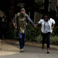 A security agent evacuates an injured woman from the scene where explosions and gunshots were heard at the Dusit hotel compound in Nairobi Jan. 15. | REUTERS