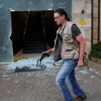 Serge Medic, the Swiss owner of a security company, carries his pistol as he walks at the scene where explosions and gunshots were heard at the Dusit hotel complex in Nairobi Jan. 15. | REUTERS