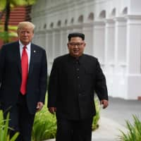 North Korean leader Kim Jong Un walks with U.S. President Donald Trump during a break in talks at their historic summit, at the Capella Hotel on Sentosa island in Singapore last June. | AFP-JIJI