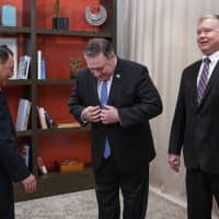 U.S. Secretary of State Mike Pompeo and special representative Stephen Biegun (right) greet North Korean lead nuclear negotiator Kim Yong Chol at The Dupont Circle Hotel in Washington on Friday. | AP