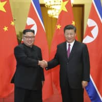 Chinese President Xi Jinping (right) shakes hands with North Korean leader Kim Jong Un during a welcome ceremony at the Great Hall of the People in Beijing last June. South Korean media reported late Monday,  that North Korean leader Kim Jong Un may be on his way to Beijing for his fourth summit with Xi. | JU PENG / XINHUA / VIA AP