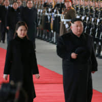 North Korean leader Kim Jong Un and his wife, Ri Sol Ju, inspect an honor guard before leaving Pyongyang for a visit to China on Monday. | REUTERS