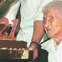 Jeanne Calment, French pensioner and the world's oldest person, looks at her birthday cake upon turning 121 years old during a ceremony held in her honour at Arles City Hall in the southern France in 1996. What if Calment's longevity record was a fraud? Russian researchers have concluded an incredible sleight of hand between the Frenchwoman and her daughter, provoking interest and controversy in the scientific community. Jeanne Calment died at the age of 122 years and 164 days in 1997 — a world record of longevity of all genders. | AFP-JIJI