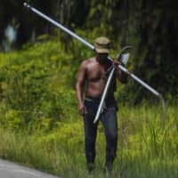 A worker, carrying tools to harvest oil palm fruit, walks along a road at a plantation in Subulussalam district in Aceh province, Indonesia, on Thursday. | AFP-JIJI