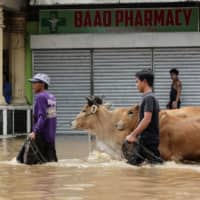 Filipinos in the flooded town of Baao in Camarines Sur province on Monday | AFP-JIJI