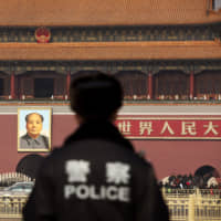 A police officer stands guard in front of a portrait of former Chinese leader Mao Zedong at Tiananmen Square in Beijing, China last February.  | Bloomberg