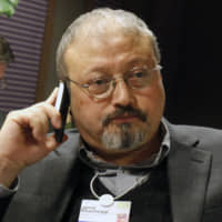 Saudi journalist Jamal Khashoggi speaks on his cellphone at the World Economic Forum in Davos, Switzerland, in 2011. Khashoggi disappeared on Oct. 2 after visiting his country's consulate in Istanbul. | AP