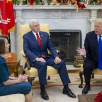 U.S. President Donald Trump speaks while then-House Minority Leader Nancy Pelosi and Vice President Mike Pence listen during a meeting at the Oval Office of the White House in Washington on Dec. 11. | BLOOMBERG