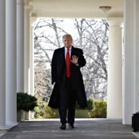U.S. President Donald Trump waves as he walks through the Colonnade from the Oval Office of the White House on arrival to announce a deal to temporarily reopen the government Friday from the Rose Garden of the White House in Washington. | AP