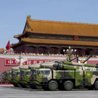 Chinese military vehicles carrying DF-21D anti-ship ballistic missiles, potentially capable of sinking a U.S. Nimitz-class aircraft carrier in a single strike, travel past Tiananmen Gate during a military parade to commemorate the 70th anniversary of the end of World War II in Beijing in 2015. | AP