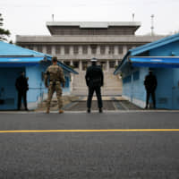 U.S. and South Korean soldiers stand guard next to the meeting rooms that straddle the border between the two Koreas in the truce village of Panmunjom in the Demilitarized Zone in Paju, South Korea, in April 2017. | BLOOMBERG