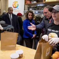 House Speaker Nancy Pelosi (center) and Chef Jose Andres (second from right) arrive to give out food at World Central Kitchen, the not-for-profit organization started by Chef Jose Andres, Tuesday in Washington. | AP