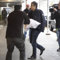 Michael Cohen arrives at his home in New York with his left arm in a sling supported by a pillow Friday. Democrats are vowing to investigate whether President Donald Trump directed Cohen, his personal attorney, to lie to Congress about a Moscow real estate project, calling that possibility a 'concern of the greatest magnitude.' | AP