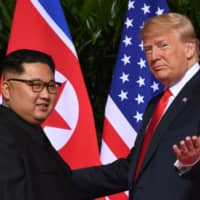 U.S. President Donald Trump gestures as he meets with North Korean leader Kim Jong Un at the start of their historic U.S.-North Korea summit at the Capella Hotel on Sentosa island in Singapore last June. Trump said Sunday negotiations are underway on the location of the next summit with Kim. | AFP-JIJI