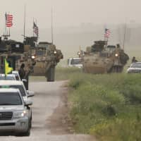 Kurdish fighters from the People's Protection Units (YPG) head a convoy of U.S. military vehicles in the Syrian town of Darbasiya, next to the Turkish border, in April 2017. | REUTERS