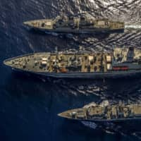 The HMS Argyll (bottom) takes part in a replenishment at sea with the USS McCampbell (top) and USNS Henry J Kaiser while operating in the South China Sea on Saturday. | ROYAL NAVY