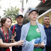 Anastasia Vashukevich speaks to journalists while being escorted by Thai immigration officers from the Immigration Detention Center in Bangkok on Thursday. | AP
