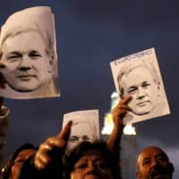Supporters of WikiLeaks founder Julian Assange demonstrate in front of presidential palace regarding his Ecuadorian citizenship, in Quito last October. | REUTERS