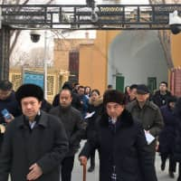 Imams and government officials pass under security cameras as they leave the Id Kah Mosque during a government organized trip in Kashgar, Xinjiang Uighur Autonomous Region, China, Friday. | REUTERS