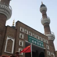 The Chinese national flag flies outside the mosque at the Xinjiang International Grand Bazar during a government-organized trip in Urumqi, Xinjiang Uighur Autonomous Region, China, on Jan. 3. | REUTERS