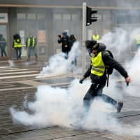 A protester returns a tear gas canister during a demonstration of the 'yellow vests' movement in Strasbourg, France, Saturday. | REUTERS