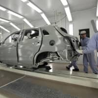 Workers check a Mitsubishi Motors Corp. sports utility vehicle at the company's plant in Okazaki, Aichi Prefecture. | BLOOMBERG