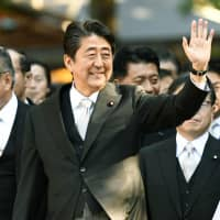Prime Minister Shinzo Abe is escorted by a Shinto priest as he visits the Grand Shrines of Ise in Mie Prefecture on Friday. | KYODO