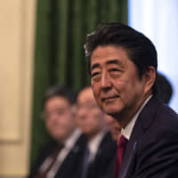Prime Minister Shinzo Abe listens during a meeting with his U.K. counterpart Theresa May in London on Jan. 10. | BLOOMBERG