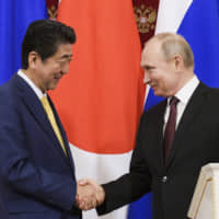 Prime Minister Shinzo Abe greets Russian President Vladimir Putin at a joint news conference after their talks in Moscow on Tuesday. | AP