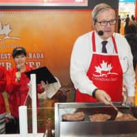 Lawrence MacAulay, Canadian Minister of Agriculture and Agri-Food, grills Canadian beef at the Foodex Japan food trade fair held in the city of Chiba in March. Canada is eager to boost exports of farm produce to Japan under a new Pacific trade pact that no longer includes the United States. | KYODO