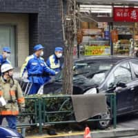 A car is seen on a sidewalk near JR Shinjuku Station in Tokyo on Wednesday after its diver hit and injured five people. | KYODO