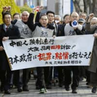 Plaintiffs walk toward the Osaka District Court on Tuesday before a ruling in a lawsuit filed by Chinese citizens seeking compensation for forced labor during World War II. | KYODO