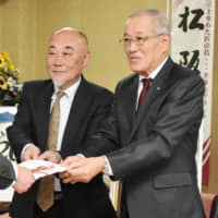 Takao Uno (right), former head of Hagetemo Katsura wo Kaburan Kai, a group of bald men working for traffic safety that dissolved in November, and Toru Kadoya, the former vice head, hand donations to an official at the Matsusaka Municipal Government building in Mie Prefecture in December. | CHUNICHI SHIMBUN
