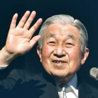 Emperor Akihito waves to well-wishers from the balcony of the Imperial Palace in Tokyo on Wednesday. | AFP-JIJI