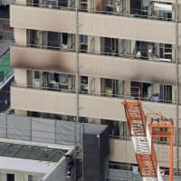 Two people were killed and 13 were injured in a fire early Friday at this lodging house in Yokohama. | KYODO