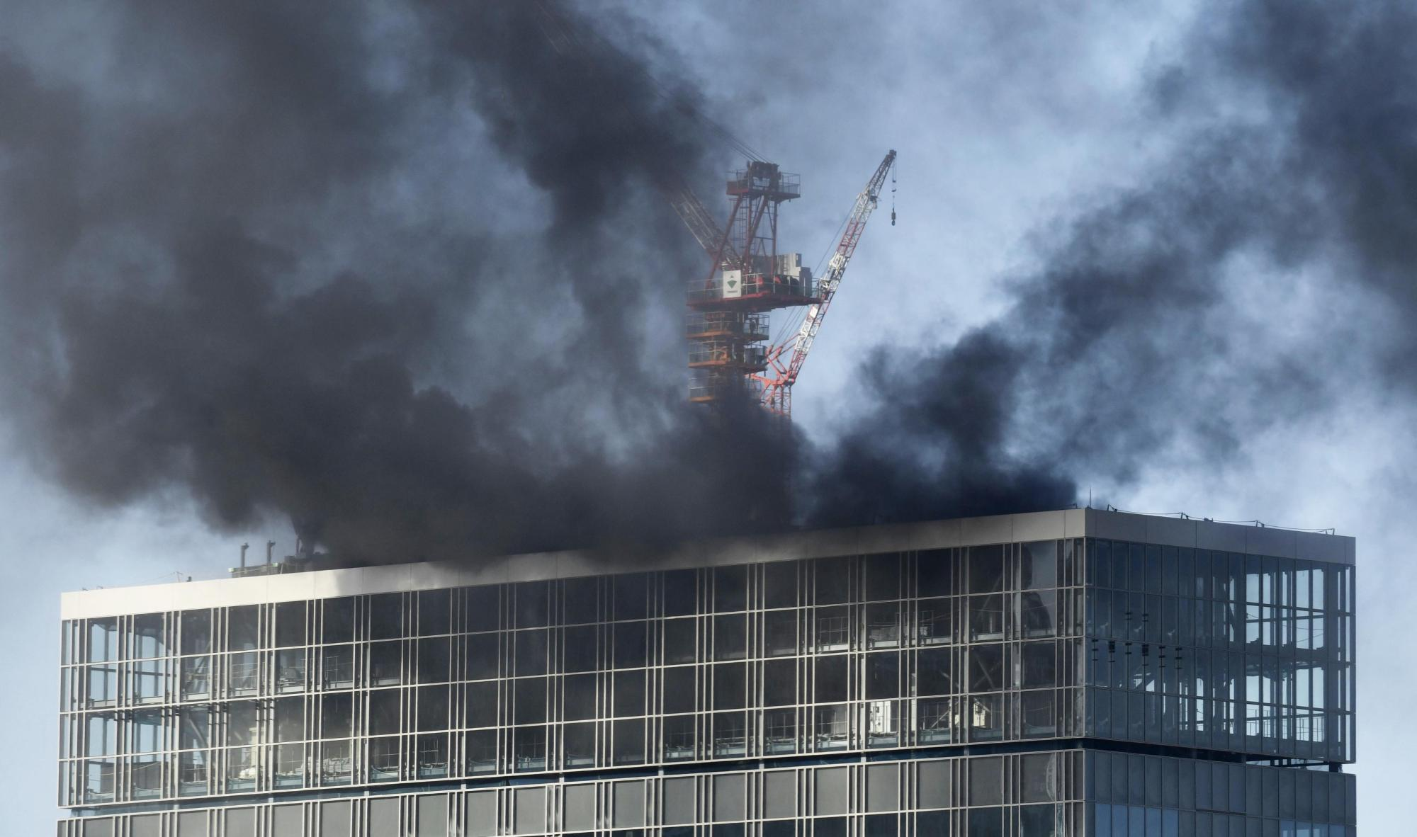Black smoke billows from a high-rise building under construction near JR Shimbashi Station in Tokyo on Friday. | KYODO