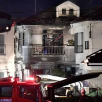Firefighters investigate a home where a fire broke out in the early hours of Sunday in Hino, Tokyo. | KYODO