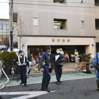 Police officers and firefighters are seen Friday in front of a lodging house in Yokohama where a fire broke out earlier in the day, killing two people. | KYODO