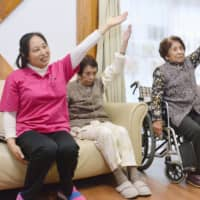 Technical trainees from China exercise with residents of a nursing care home for people with dementia in Nobeoka, Miyazaki Prefecture, in November. | KYODO