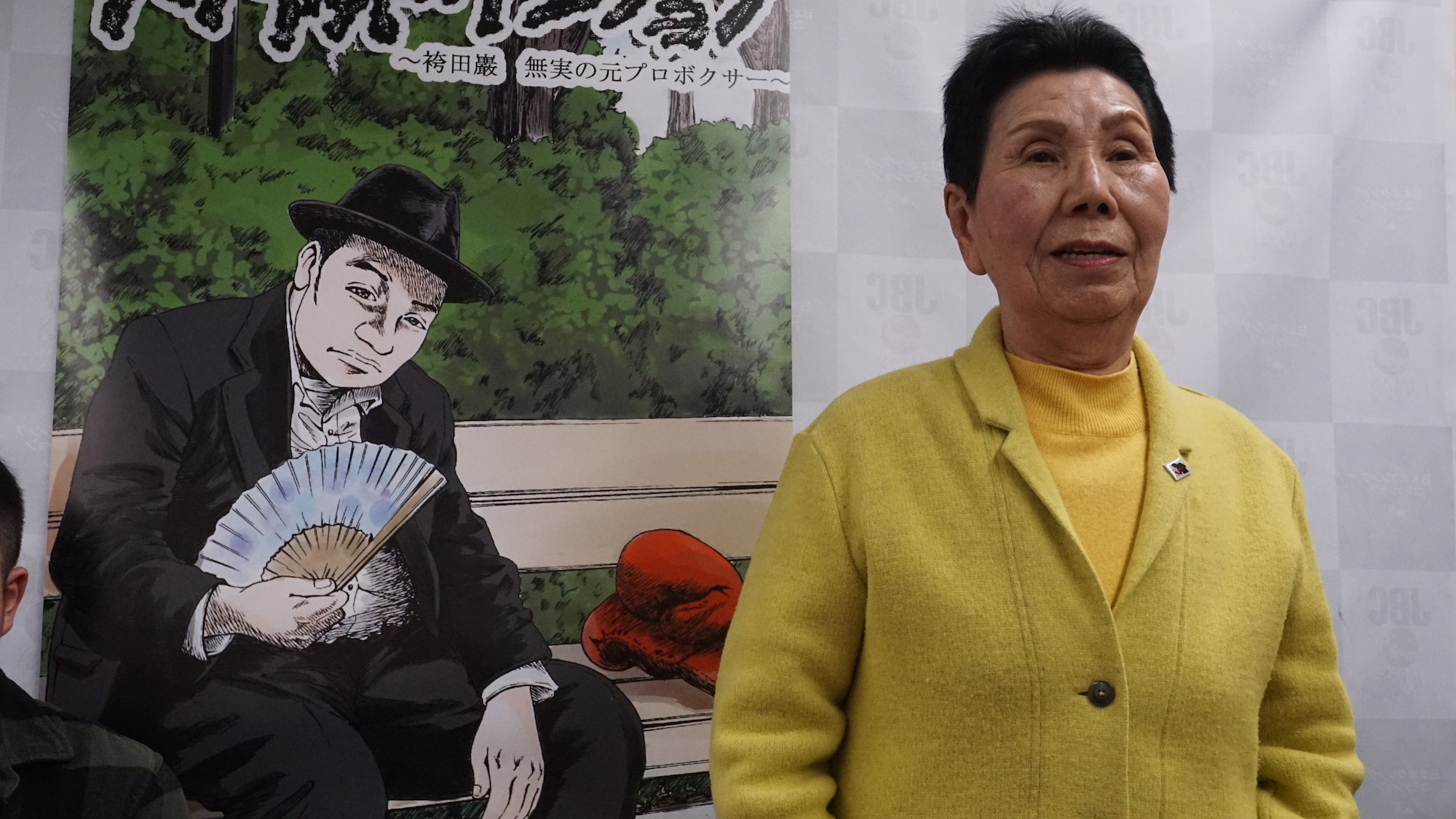 Hideko Hakamada, elder sister of freed death-row inmate Iwao Hakamada, speaks at a news conference Wednesday in Tokyo in front of a poster for the new manga series that depicts the ex-boxer's life. | MAGDALENA OSUMI