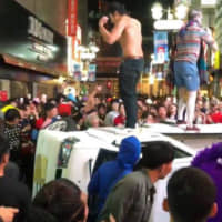 Halloween revelers stand on a small truck that was overturned in Shibuya Ward, Tokyo, a mecca for the celebrations, in the early hours of Oct. 28. | YU MENTAL CLINIC / VIA KYODO