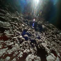The rocky surface of asteroid Ryugu is seen in this photo taken in September by a robot launched from the Hayabusa2 spacecraft. | JAXA VIA KYODO