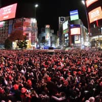 Thousands of revelers fill the Shibuya 'scramble' crossing and shout the countdown to a new year.    KYODO