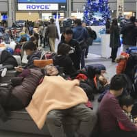 People who stayed overnight at New Chitose Airport in Hokkaido crowd the lobby of the airport Sunday morning after some 2.000 travelers were left stranded due to heavy snow that led to flight cancelations. | KYODO